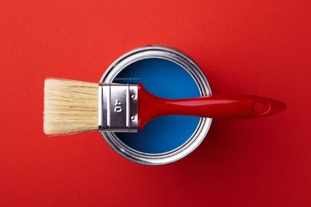 Can of classic blue paint with brush on red background. Top view. Reklamní fotografie - 137323573