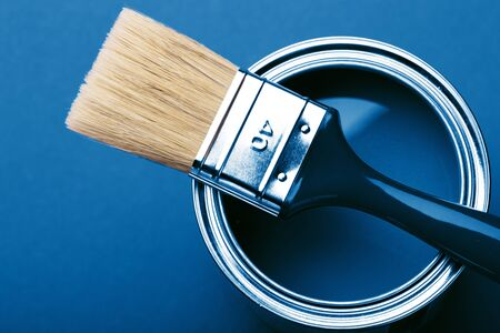 Can of blue paint with brush on blue background. Top view.