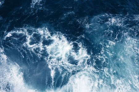 Top view on blue ocean waves and foam.