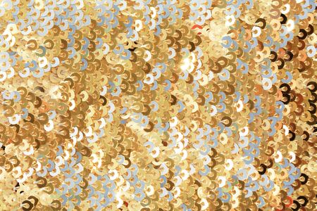 Sparkling golden sequined fabric. Glittering textile background.