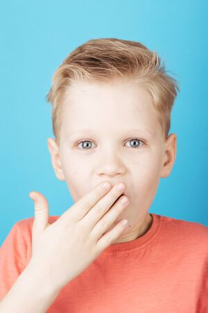 Portrait of cute surprised boy covering his mouth with his hand with stylish hairstyle in coral T-shirt