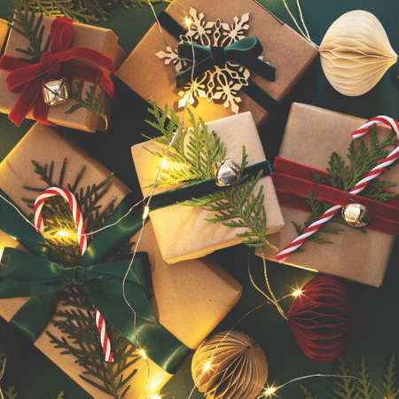 Many Christmas gift boxes tied velvet ribbons with paper decorations in garland lights.