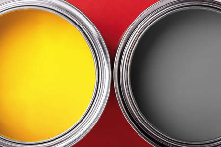 Cans of yellow and gray paint on red background. Top view, minimal.
