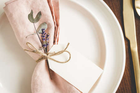 Close up view on plates arranged with a pink linen napkin, floral decor and tag. Banque d'images