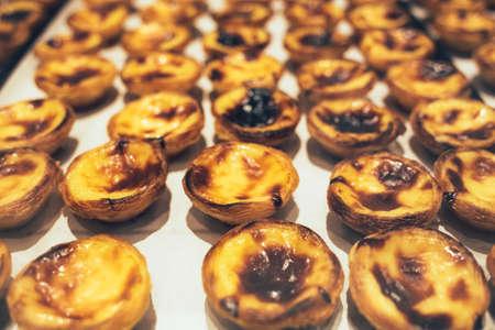 Traditional Portuguese dessert - Pastel de nata on bakery shelve.