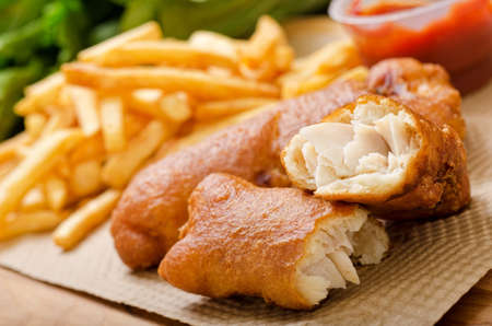 A delicious crispy battered deep fried fish and chips with greens and ketchup.