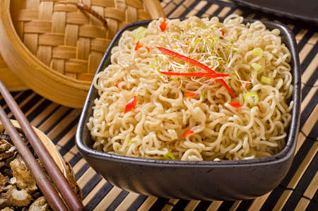 thai noodle soup: A bowl of asian style noodles with bamboo steamer and chopsticks