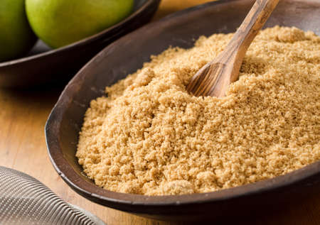 granulated: A bowl of brown sugar with green apples, wooden spoon and sieve  Stock Photo