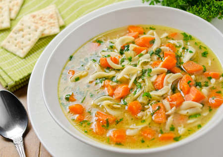 Hearty home made chicken noodle soup with soda crackers. photo
