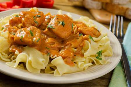 Chicken paprikash with egg noodles and red pepper. Stock Photo