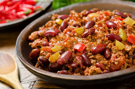 chili: A hearty bowl of chili con carne with hot peppers.