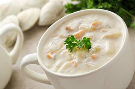 A bowl of creamy New England clam chowder with whole clams and parsley. photo