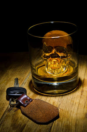 A glass of whiskey with a skull ice cube with car keys. Stock Photo