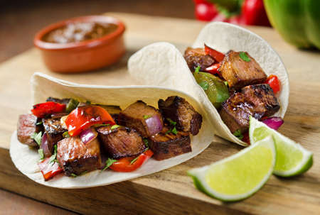 and delicious food: Two beef fajitas with red onion, peppers, cilantro, and lime.