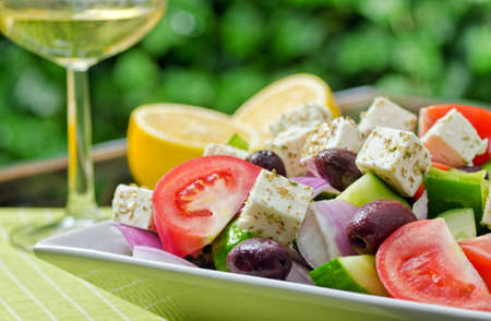 A summer fresh greek salad with tomato, cucumber, green pepper, red onion, kalamata olive, and feta cheese.