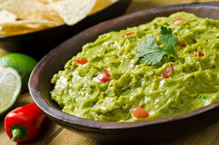 mexican food: A bowl of creamy guacamole dip with peppers, tomato, cilantro, and lime.