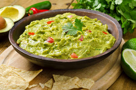 dip: Guacamole with avocado, lime, tomato, and cilantro with tortilla chips. Stock Photo
