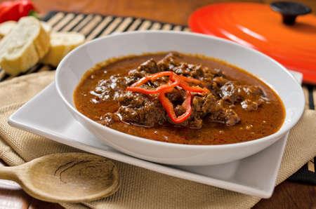 Een kom van authentieke Hongaarse goulash met paprika en pepers.