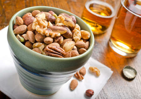 vitamin bottle: A bowl of mixed nuts with beer.