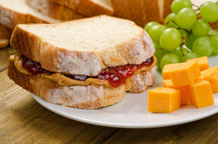 peanut butter and jelly sandwich: A nutritious peanut butter and jelly sandwich with cheddar cheese and grapes  Stock Photo