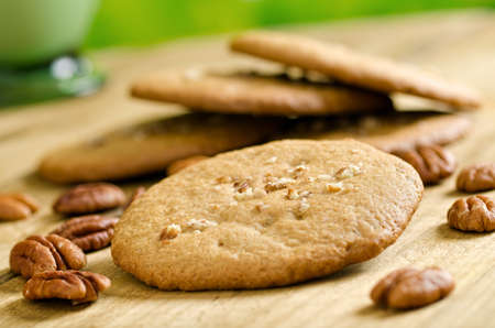 pecan: A stack of freshly baked pecan cookies with whole pecans.