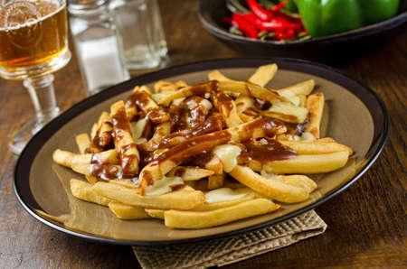 Een plaat van heerlijke poutine met frietjes, jus en kaas wrongel