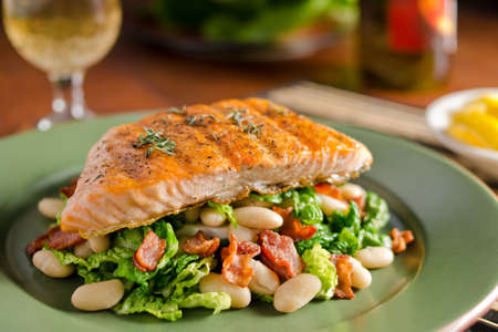 bacon baked beans: Grilled salmon with white beans, bacon, and kale. Stock Photo