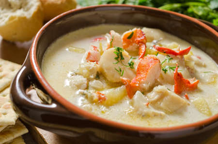 lobster: A steaming hot bowl of seafood chowder with lobster, clams, haddock, scallops, and potato. Stock Photo