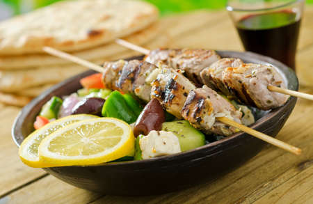 Grilled pork souvlaki skewers with greek salad and lemon. Stock Photo