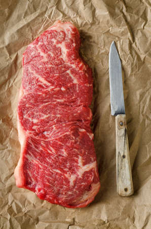 A perfectly  marbled strip loin steak on crumpled butcher paper with old knife  photo
