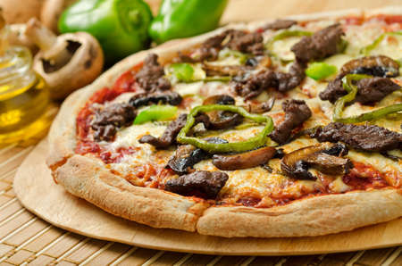 A delicious steak and mushroom pizza with green peppers and olive oil  photo