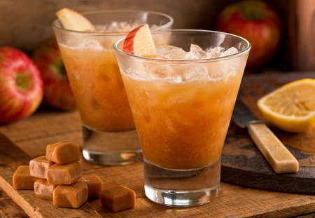 garnished: Caramel Apple Cider Cocktails on a rustic background with apples, caramels, and lemon.