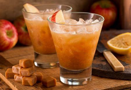 Caramel Apple Cider Cocktails on a rustic background with apples, caramels, and lemon.