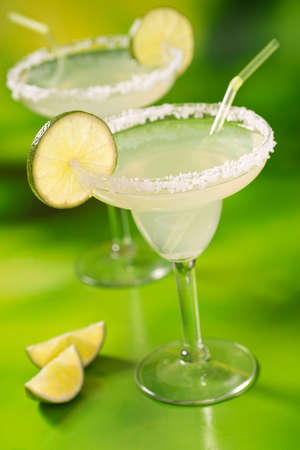 Two tequila margaritas with tequila, lime, and salt against a vibrant abstract green background.