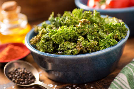 salt and pepper: A bowl of crispy delicious baked kale chips. Stock Photo