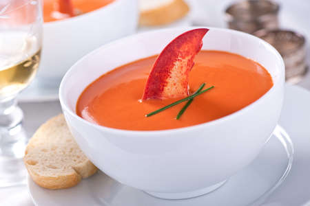 A bowl of creamy delicious lobster bisque garnished with chives and a lobster claw.