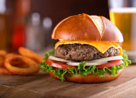 comida rapida: Una deliciosa hamburguesa con queso gourmet en un bollo de pretzel con lechuga, cebolla y tomate. Foto de archivo
