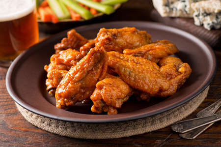 chicken dish: A plate of delicious buffalo style chicken wings with hot sauce, blue cheese, celery sticks, carrot sticks, and beer. Stock Photo