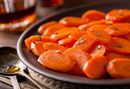 glaze: A plate of delicious maple glazed carrots with thyme. Stock Photo