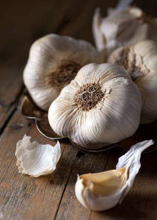Garlic bulbs and cloves on a rustic wooden harvest table. Stok Fotoğraf