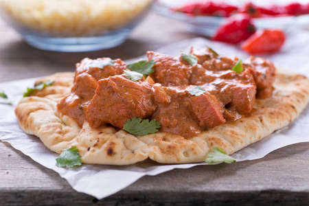 A delicious butter chicken curry served on naan bread with saffron basmati rice.