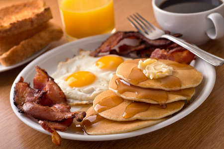 Plates: A delicious home style breakfast with crispy bacon, eggs, pancakes, toast, coffee, and orange juice.