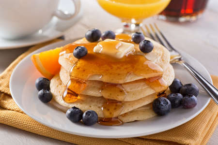 A plate of delicious pancakes with fresh blueberries and maple syrup.