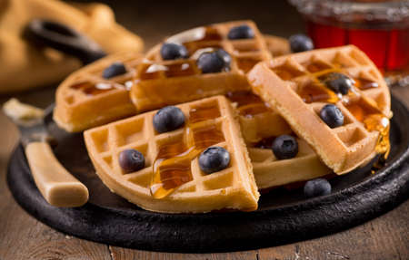 Delicious fresh homemade blueberry waffles with fresh blueberries and maple syrup.