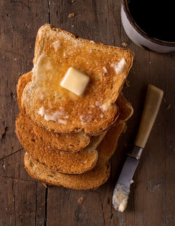 buttered: Crusty buttered toast slices on a rustic tabletop with coffee.