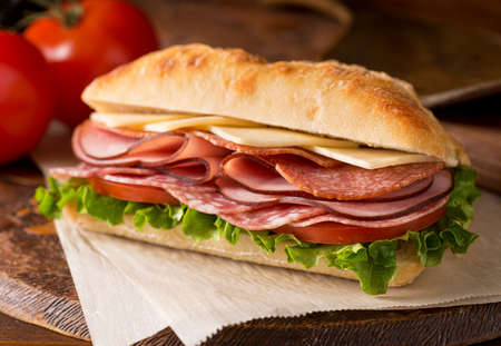 sandwich: A delicious sandwich with cold cuts, lettuce, tomato, and cheese on fresh ciabatta bread.