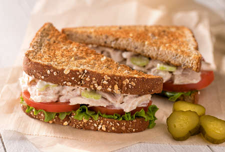fresh salad: A delicious flaked white tuna salad sandwich with tomato, lettuce, mayonnaise, and pickles.