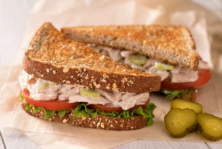 atun: Un delicioso copos blanco sándwich de ensalada de atún con tomate, lechuga, mayonesa y encurtidos. Foto de archivo