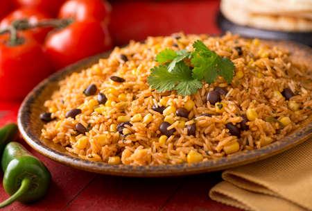 Een plaat van heerlijke authentieke Mexicaanse Rijst met zwarte bonen, maïs, knoflook en koriander.