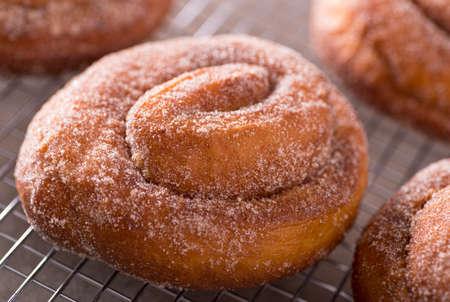 cinnamon swirl: Fresh homemade cinnamon swirl donuts on a cooling rack.
